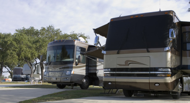 Two luxury, class A diesel-pusher motorhomes camped at a park
