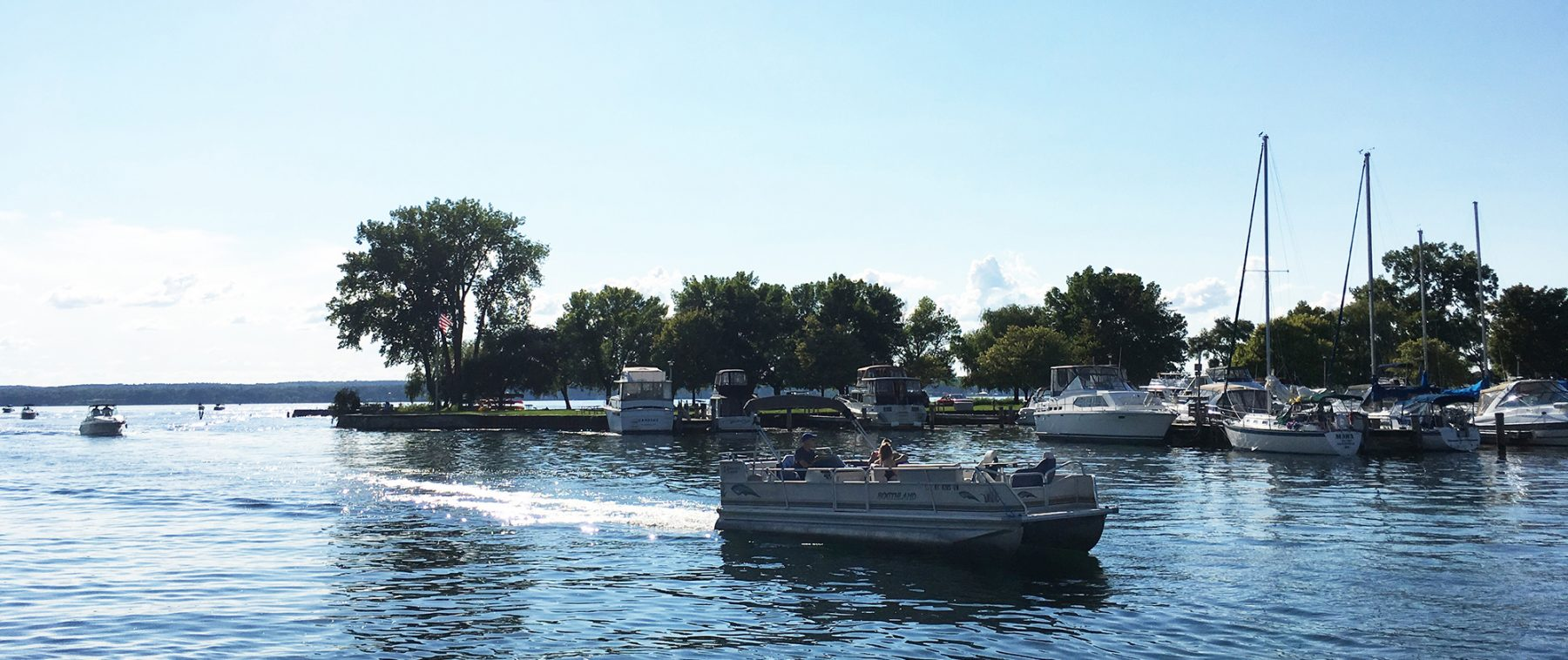 Pontoon boat entering Seneca Lake State Park Marina